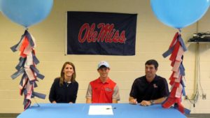 In November, Mountain Brook High School senior Griffin Riley, center, signed a National Letter of Intent to continue to his track-and-field career at Ole Miss. His parents, Shannon, left, and Richard, right, also ran at Mountain Brook.